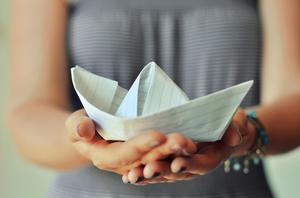 Woman holding carefully a paper boat with a red heart